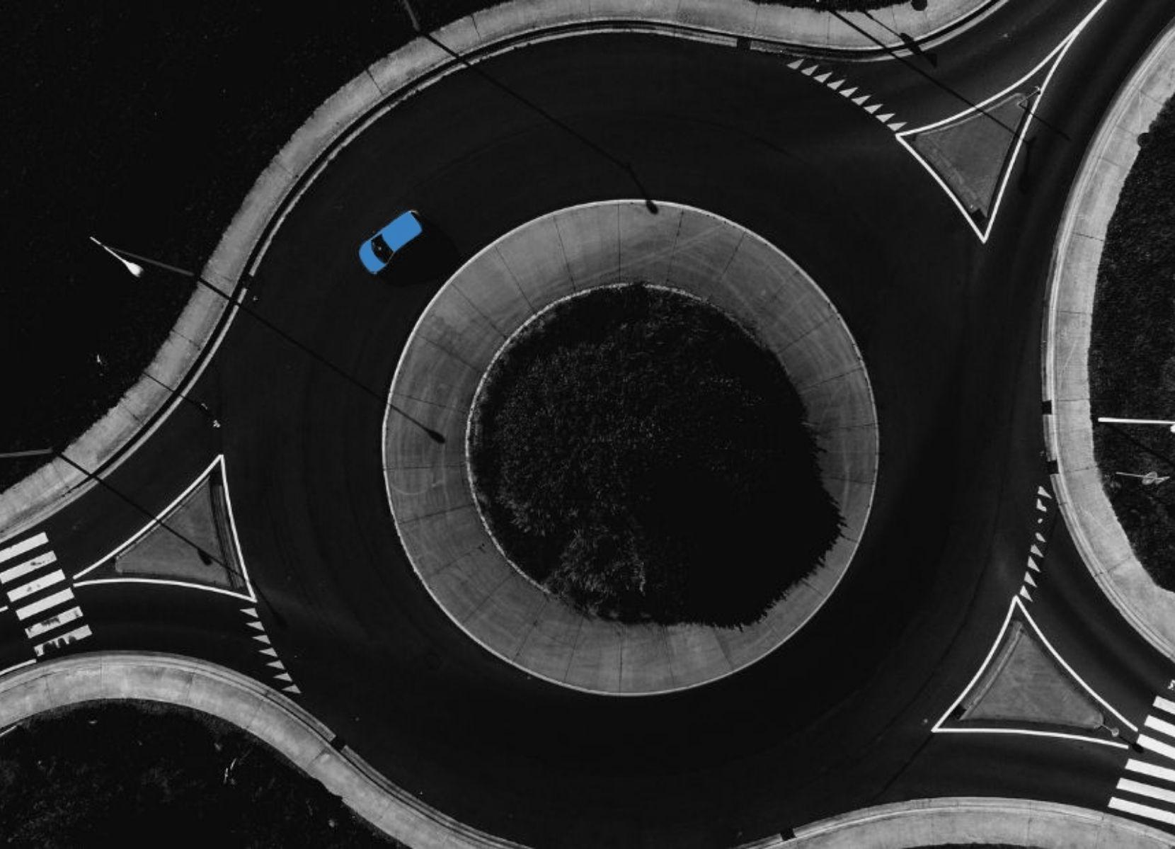 Een rotonde met een blauwe auto die staat voor het kiezen van de juiste weg.